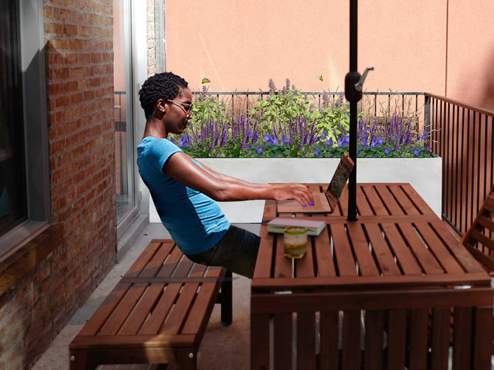 Woman on a lap top sitting on her patio with BLOOMTIME planter kit